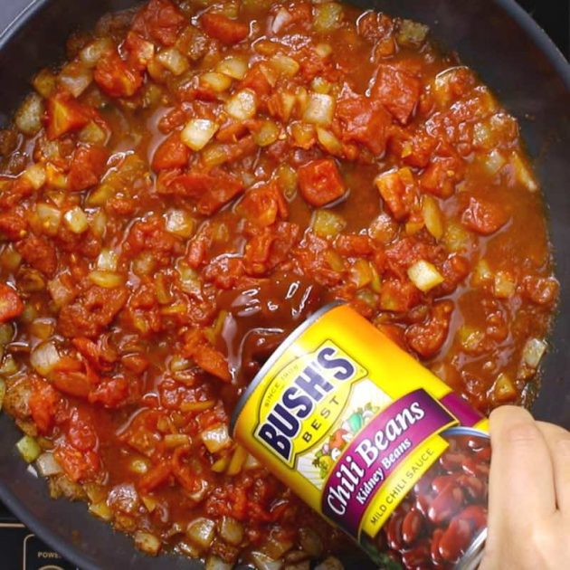 This photo shows adding Bush's Chili Beans to the chili in a skillet #AD