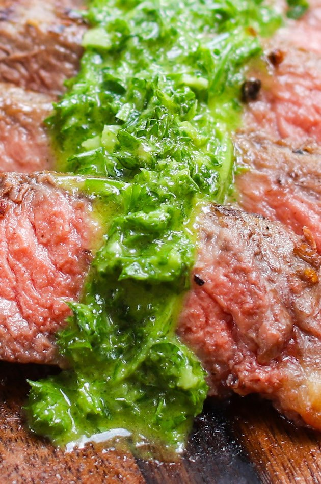 Spoon chimichurri sauce onto the pan-seared rib-eye steak