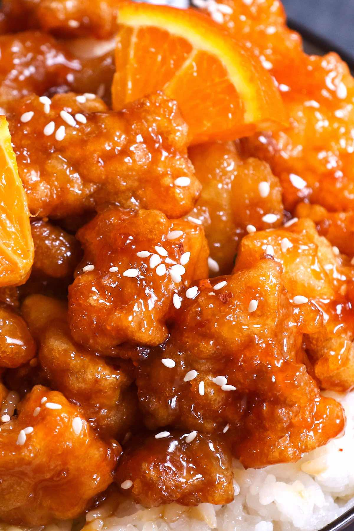 Closeup of orange chicken garnished with sesame seeds
