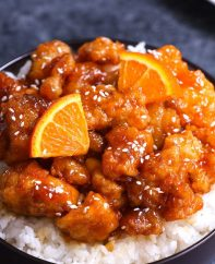 A serving of Chinese Orange Chicken garnished with sesame seeds and orange wedges on a bed of steamed rice