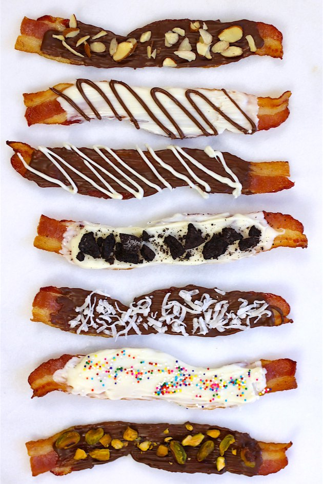 Overhead view of chocolate covered bacon made six ways with semisweet chocolate, white chocolate and toppings including pistachios, including with dark chocolate, white chocolate and toppings including pistachios, shredded coconut and sprinkles