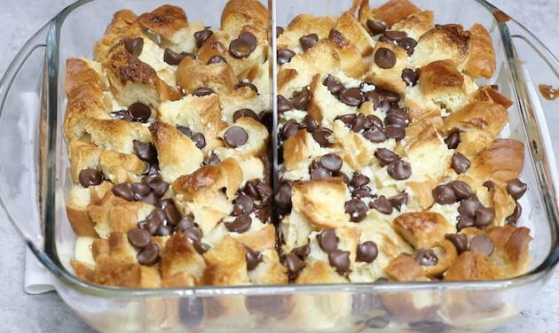 Slicing chocolate croissant bread pudding in a baking dish