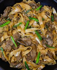 Beef chow fun noodles in a wok after being prepared showing tender strips of beef and fresh green onions for garnish