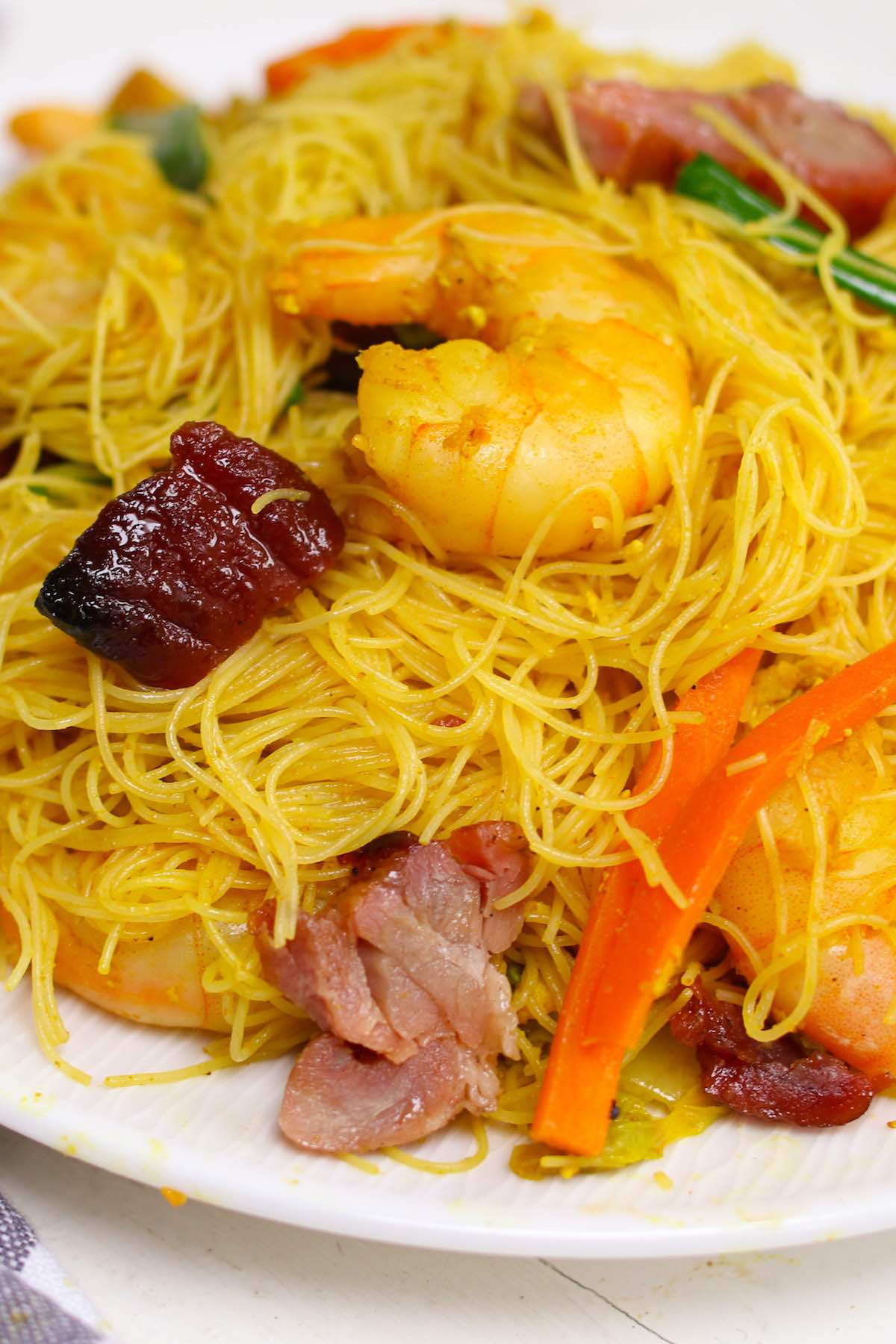Closeup of Singapore chow mei fun showing the vermicelli rice noodles, barbecue pork, shrimp and vegetables