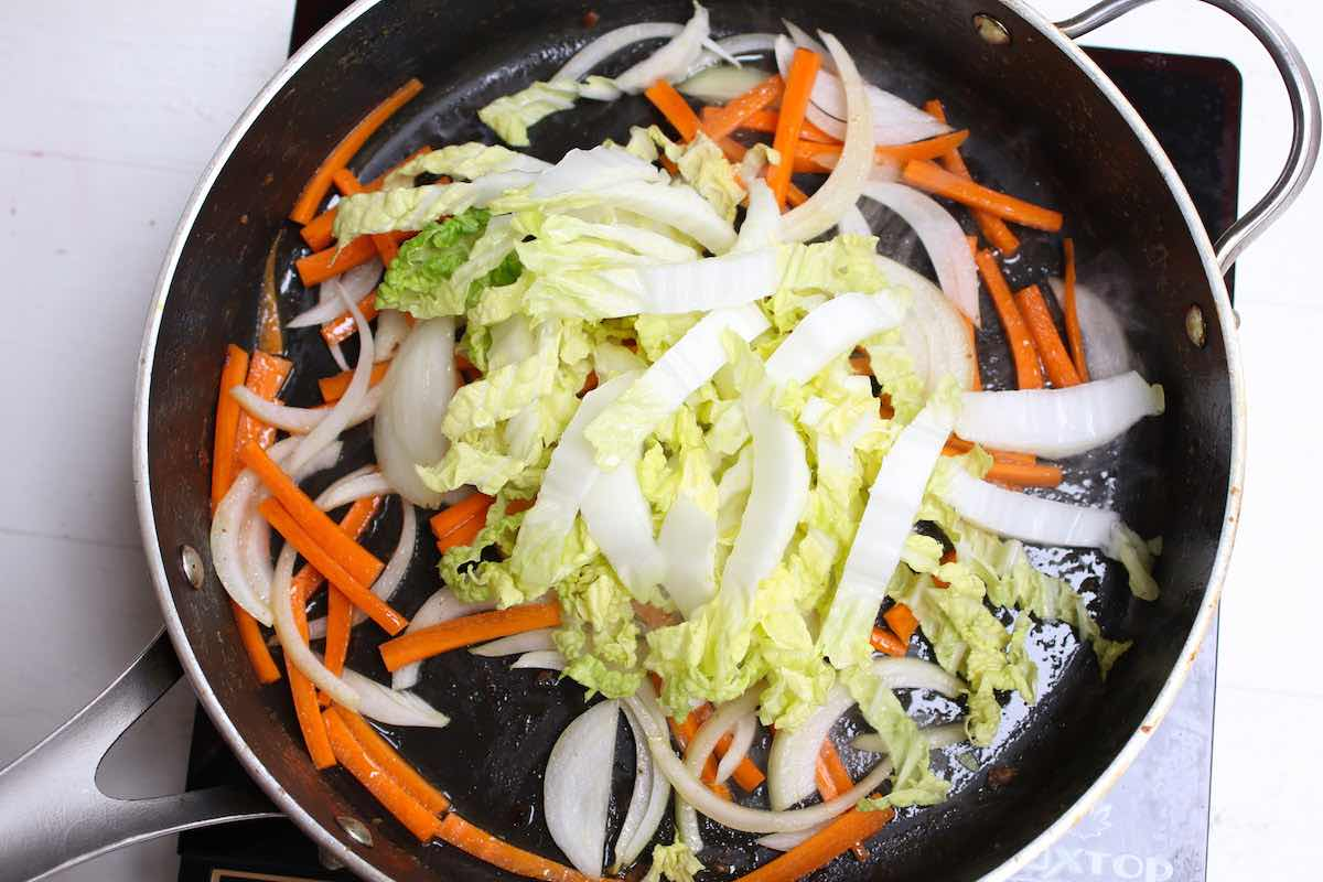 Stir frying the vegetables when making Singapore fried noodles