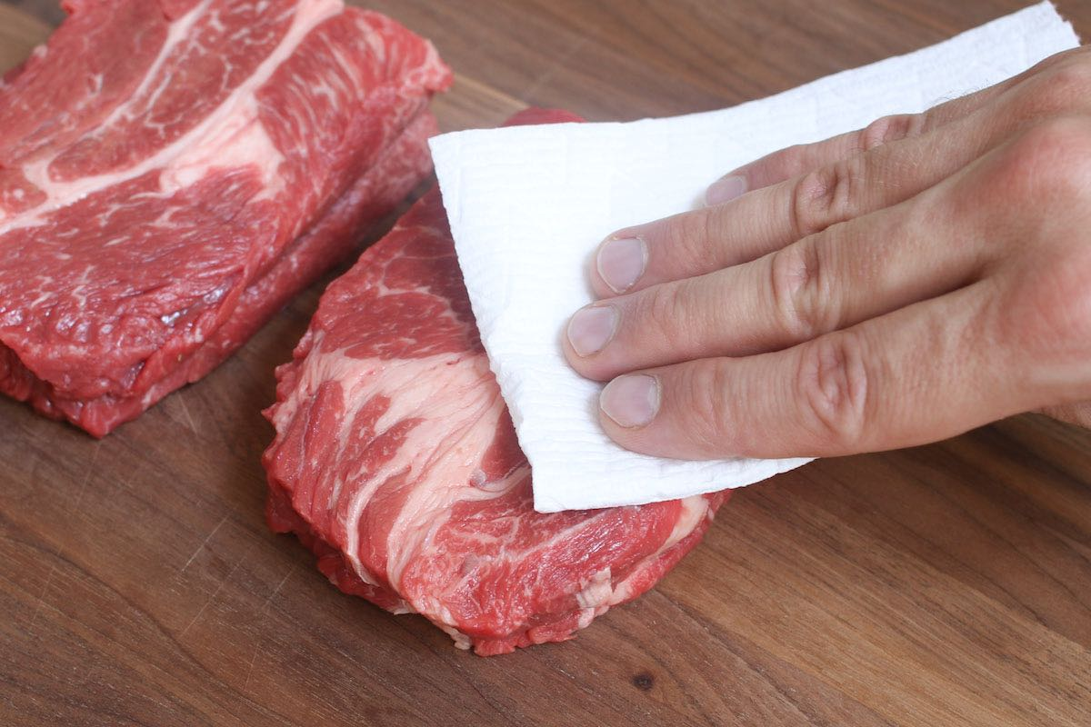 Pat drying a chuck eye steak using a paper towel to remove excess moisture that could interfere with searing