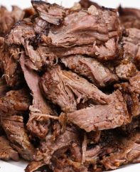 A mound of tender pulled chuck roast on a serving plate