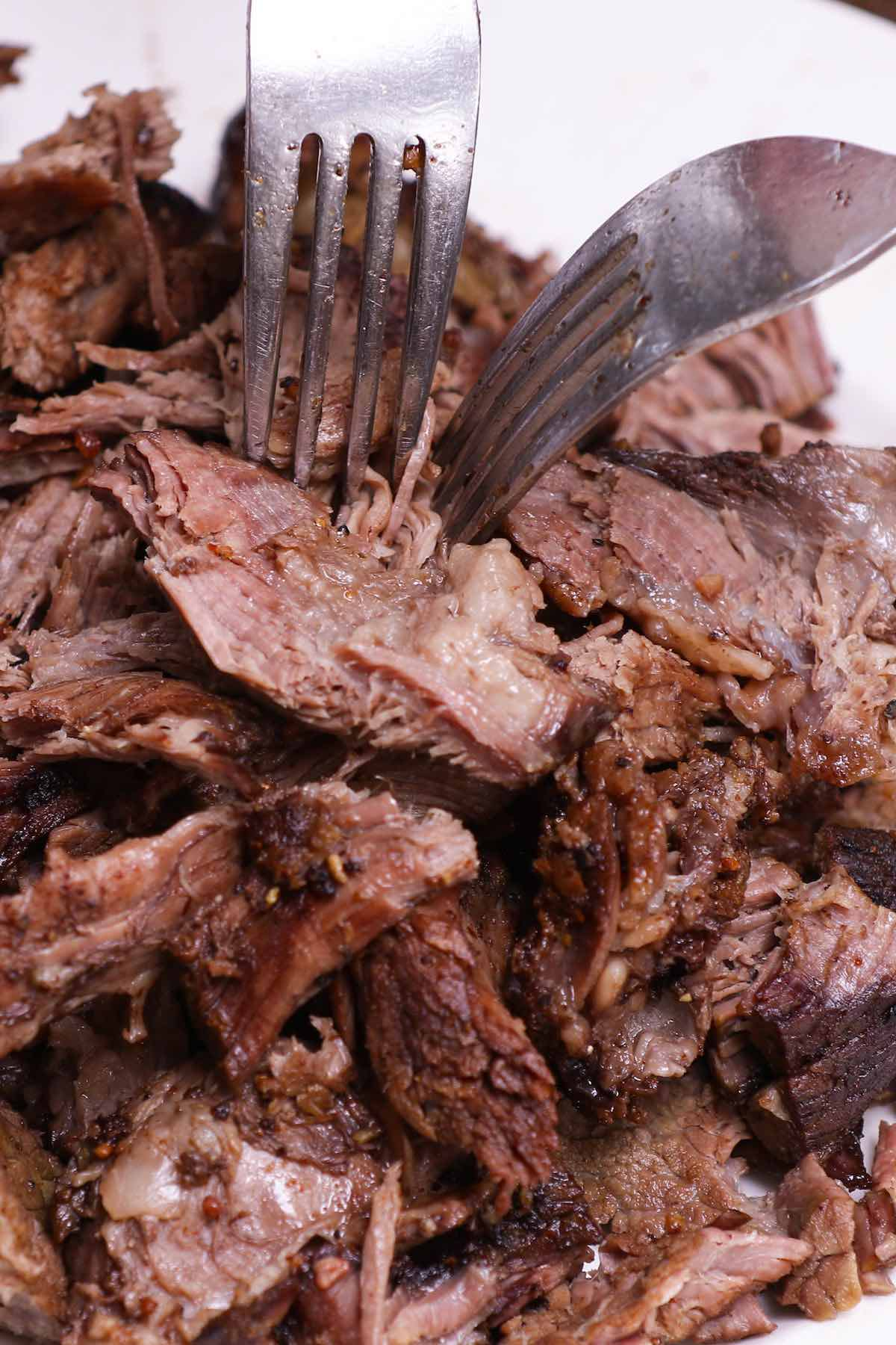Pulling smoked beef apart using two forks