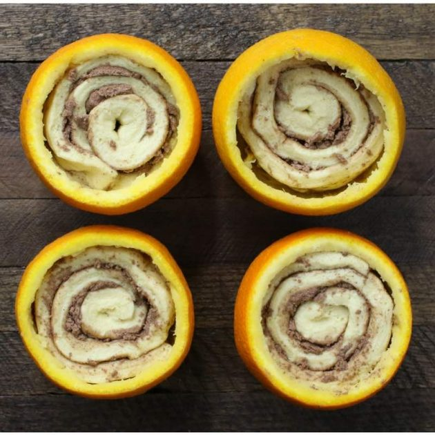 Cinnamon rolls in orange shells before baking