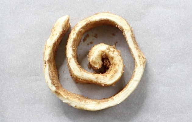 Unravelling cinnamon roll dough into a spiral pattern