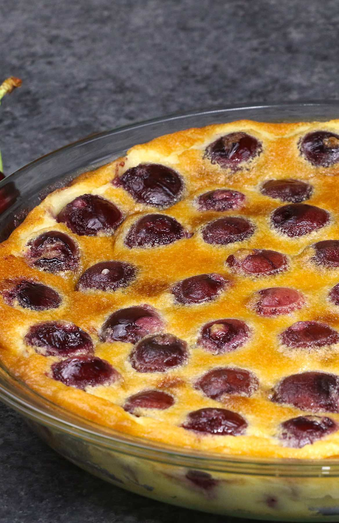 Closeup of a baked clafoutis aux cerises when done, showing the golden surface of the custard interspersed with cherries