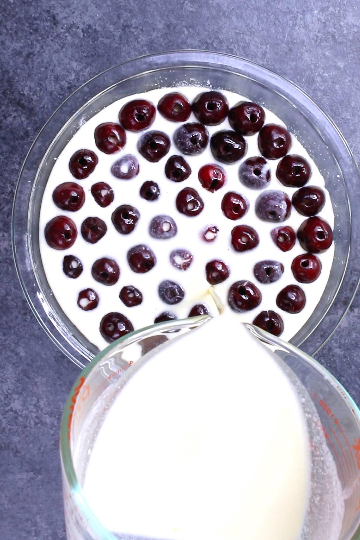 Overhead view of pouring batter on top of cherries when making a clafoutis