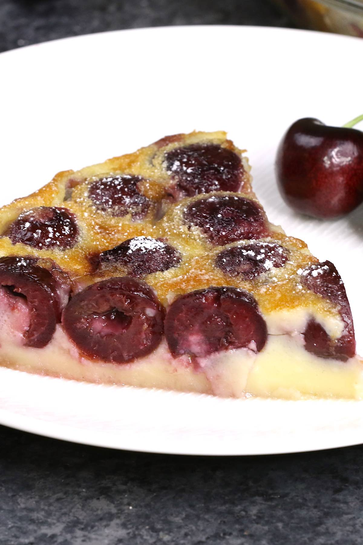 A wedge of clafoutis dusted with powdered sugar on a serving plate with a fresh cherry on the side