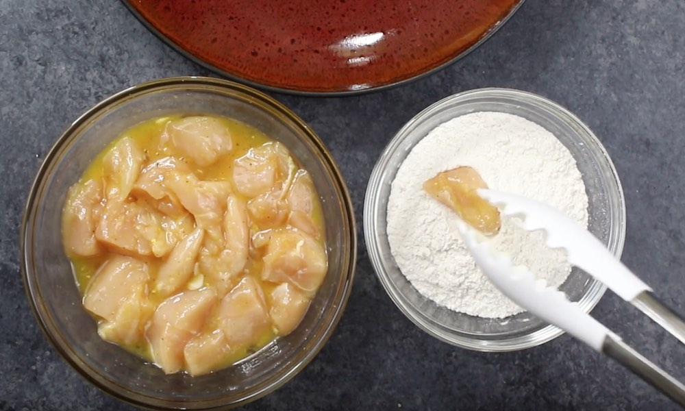 This photo shows coating the marinated chicken cubes with flour prior to frying when making Chinese Lemon Chicken
