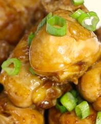 Coca Cola Chicken pan fried to tender and juicy perfection and drizzled with its own sweet and savory sauce on a serving plate, garnished with green onion for an easy party appetizer or dinner idea