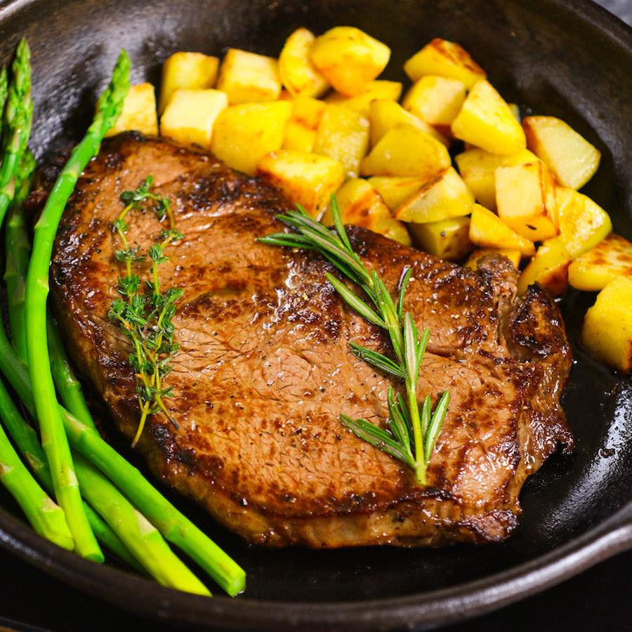 Cooked Sirloin steak with potatoes and asparagus in a cast-iron skillet