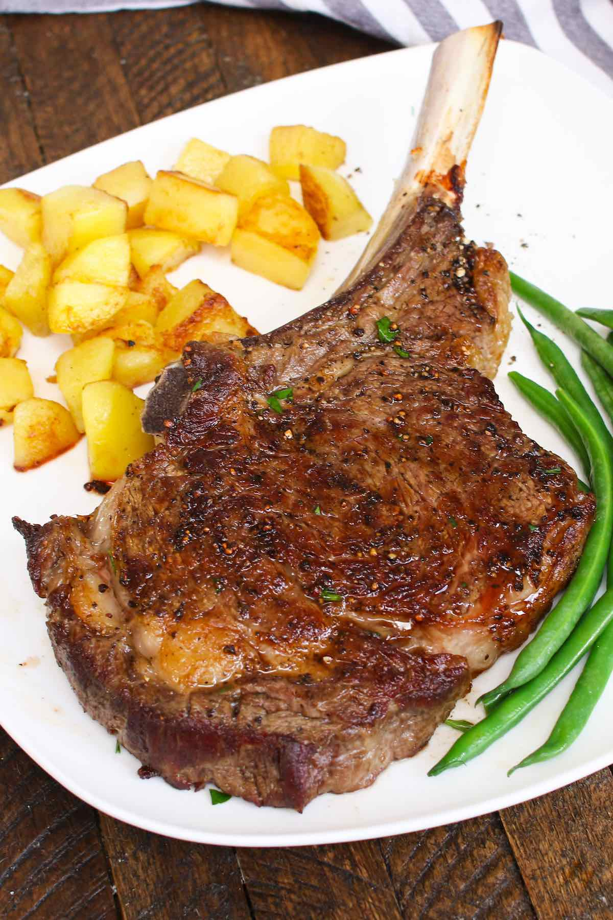 Cowboy steak cooked in the oven and served with green beans and sauteed potatoes for a delicious steak dinner