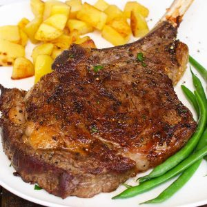 Cowboy steak on a serving plate with potatoes and green beans after being cooked in the oven