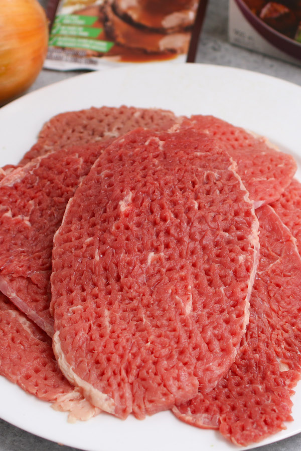 Cube steak is a sirloin or top round steak that has been tenderized by pounding it with a meat tenderizer. This process helps to tenderize and flatten the tough cut of meat and leaves small cube-shaped indentations hence the name