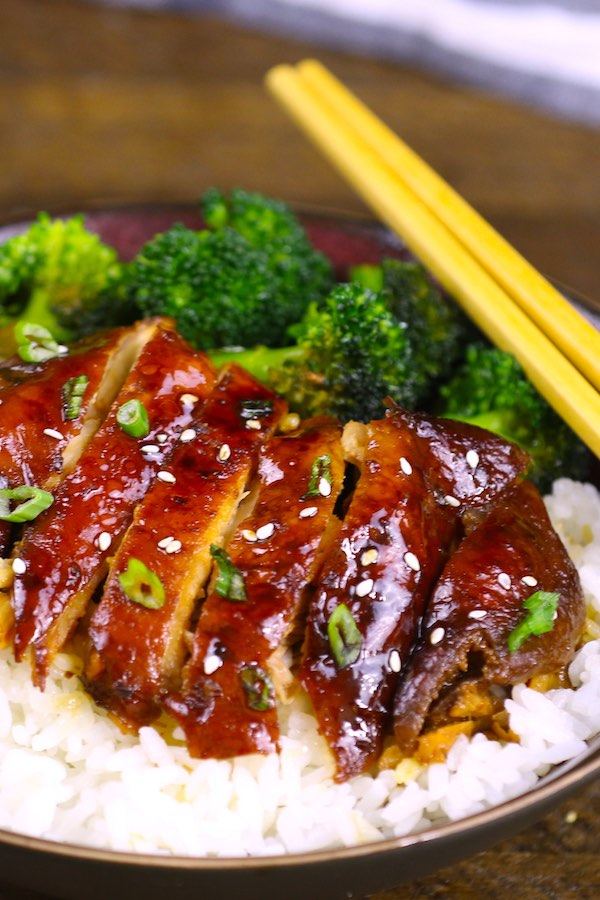 Crock Pot Teriyaki Chicken served on rice and garnished with sesame seeds and chopped green onions