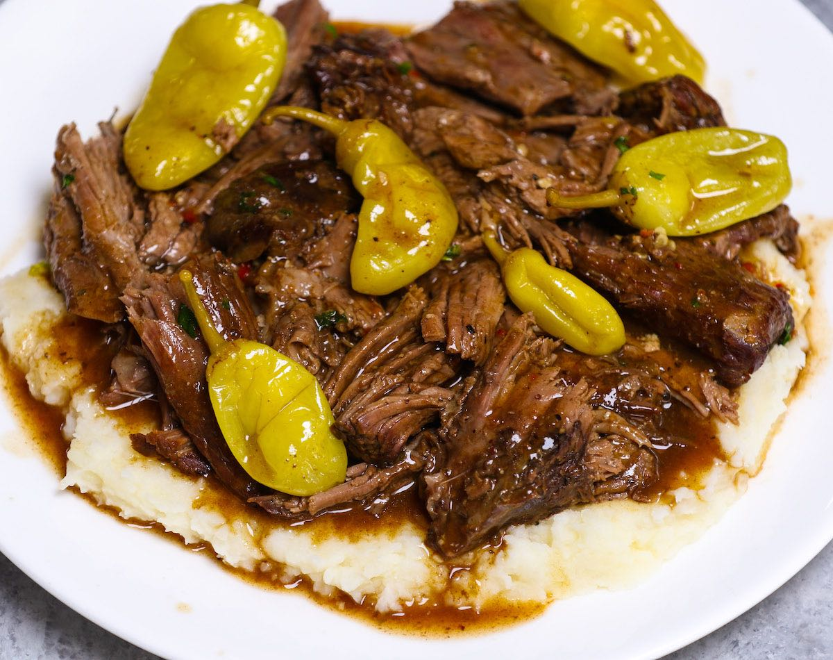 Mississippi pot roast is served over mashed potatoes on a white plate.