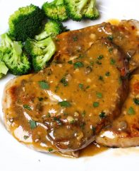 Crockpot ranch pork chops on a serving plate garnished with parsley and served with broccoli