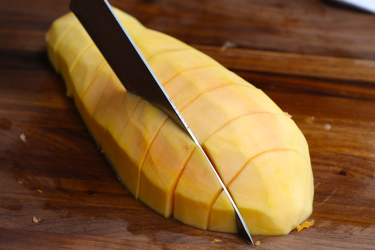 Cutting a peeled papaya into chunks using a large knife