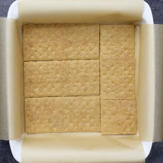 A square pan lined with parchment paper and graham cracker sheets