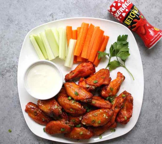 A plate of delicious game day wings with carrot and celery sticks