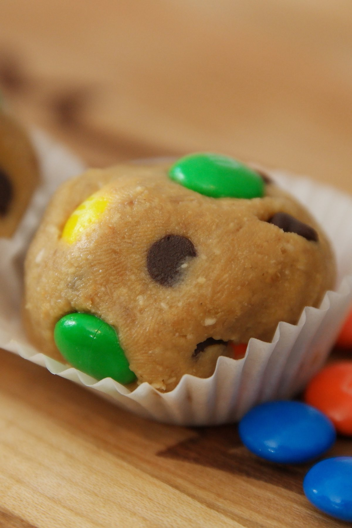Peanut butter energy bites with chocolate chips and M&Ms served in paper cups