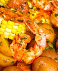 Shrimp Foil Packets being served after grilling: juicy jumbo shrimp, baby potatoes, corn and sausage with Cajun seasoning, lemon juice and fresh parsley for a delicious meal.
