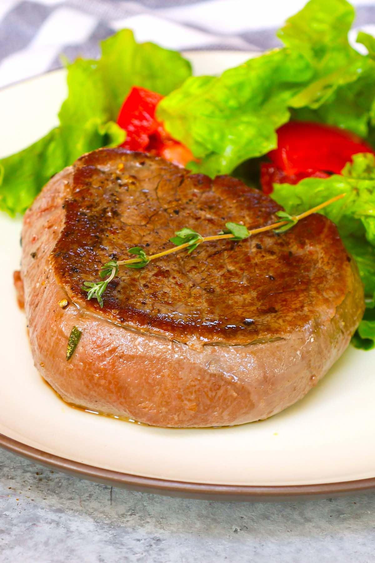 Tenderloin steak served with a side salad