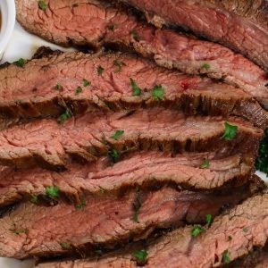 Thinly sliced flank steak cooked to medium doneness and served on a plate with a garnish of fresh thyme