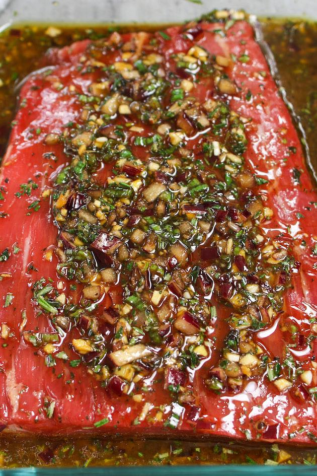 A piece of flank steak in a homemade marinade with soy sauce, olive oil, red wine vinegar, garlic and other ingredients