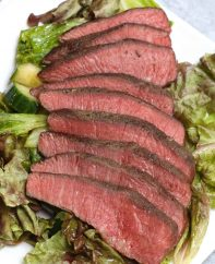 Slices of pan seared flat iron steak with a side salad