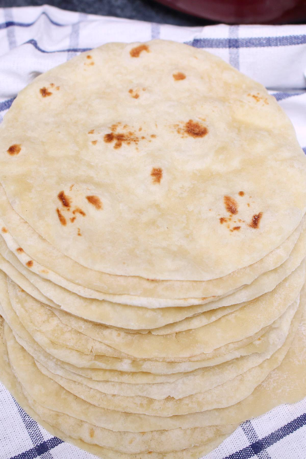 Homemade flour tortillas piled up on a towel