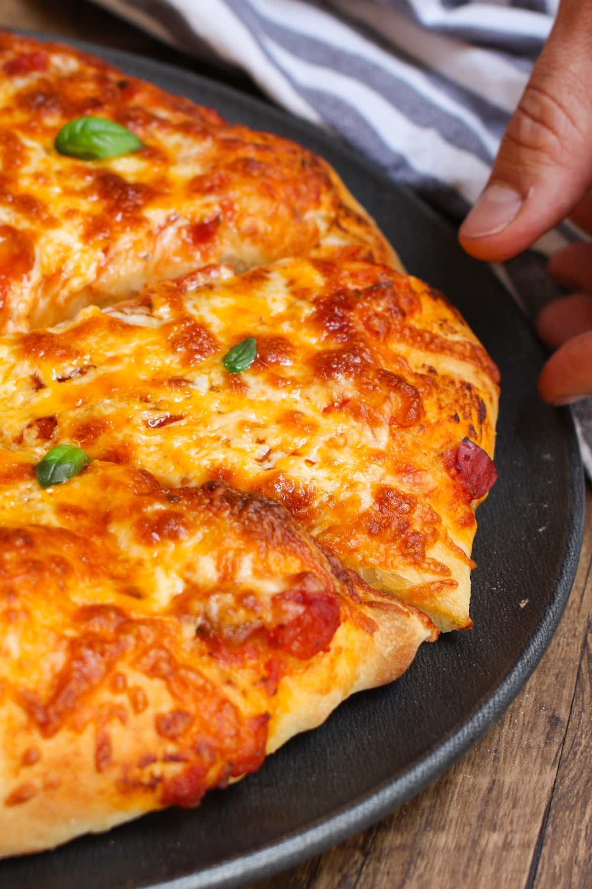 This Easy Pizza Dough Recipe makes soft and fluffy pizza crust that's beyond addictive! It's the best homemade pizza dough that has been passed down through generations. It takes 10 minutes to prepare and made by hand with 6 simple ingredients!