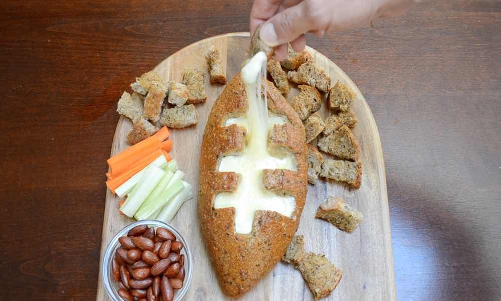 See how to make a hot cheese dip inside a bread loaf shaped like a football