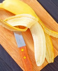 Peeling and slicing a ripe banana on a cutting board