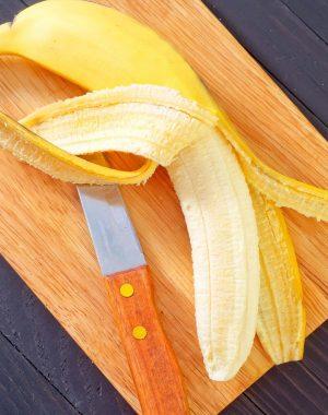 Peeling and slicing a ripe banana on a cutting board