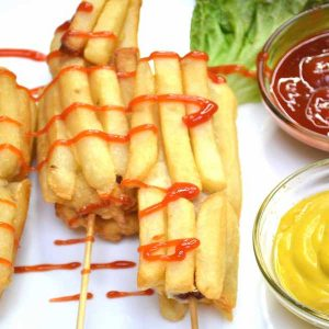Fried hot dogs on a serving plate with ketchup ad mustard dipping sauces for the perfect party appetizer