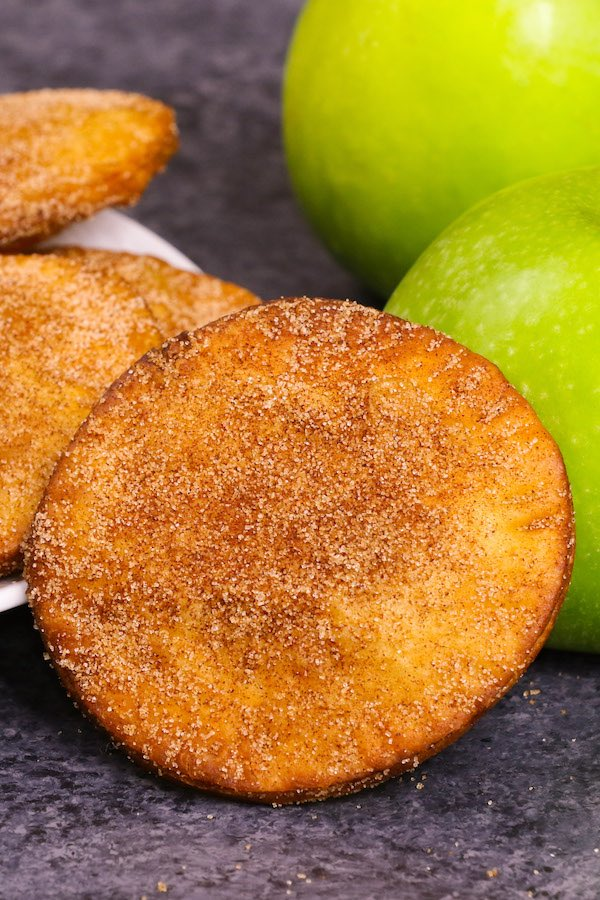 Apple hand pies dusted in cinnamon sugar with Granny Smith apples in the background