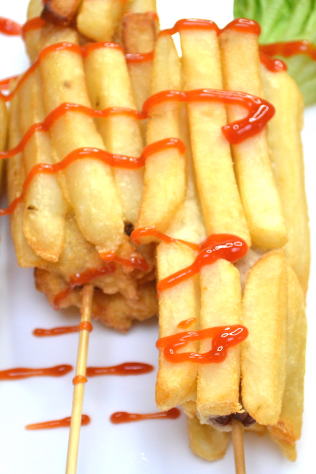 Closeup of fried hot dogs covered with french fries and dipped in ketchup