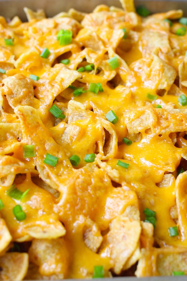 Frito Pie Casserole fresh out of the oven in a rectangular baking dish with melted cheddar cheese and topped with minced green onions