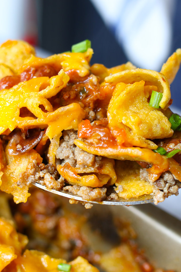 Closeup of a forkful of authentic Frito Pie showing delicious layers of corn chips, beef chili and cheese
