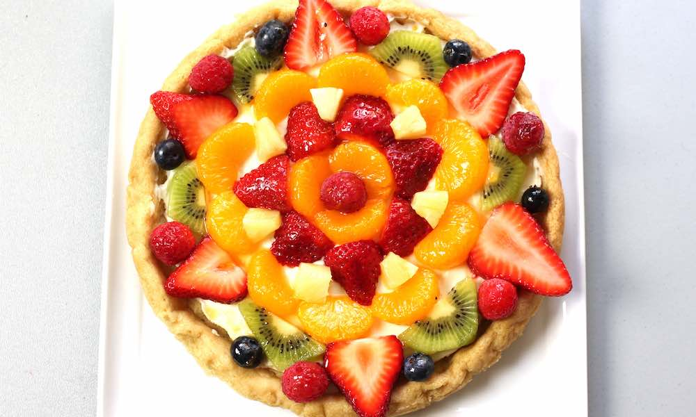 Fruit Pizza - The easiest and most unbelievably beautiful fruit pizza or fruity sugar cookie cake has a soft sugar cookie crust and smooth creamy filling, topped with fresh fruits. All you need is a few simple ingredients: refrigerated sugar cookie dough, cream cheese, sugar, vanilla extract and fruit of your choice! A simple dessert you whole family will be obsessed with. It takes only 20 minutes to make. Perfect for holiday party dessert such as Easter, Mother's Day, Father's Day or birthdays. Quick and easy, vegetarian. Video recipe. | tipbuzz.com