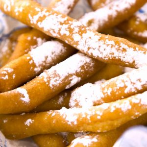 Closeup of funnel cake fries that are crispy golden on the outside and fluffy on the inside, served in a basket with a dusting of powdered sugar