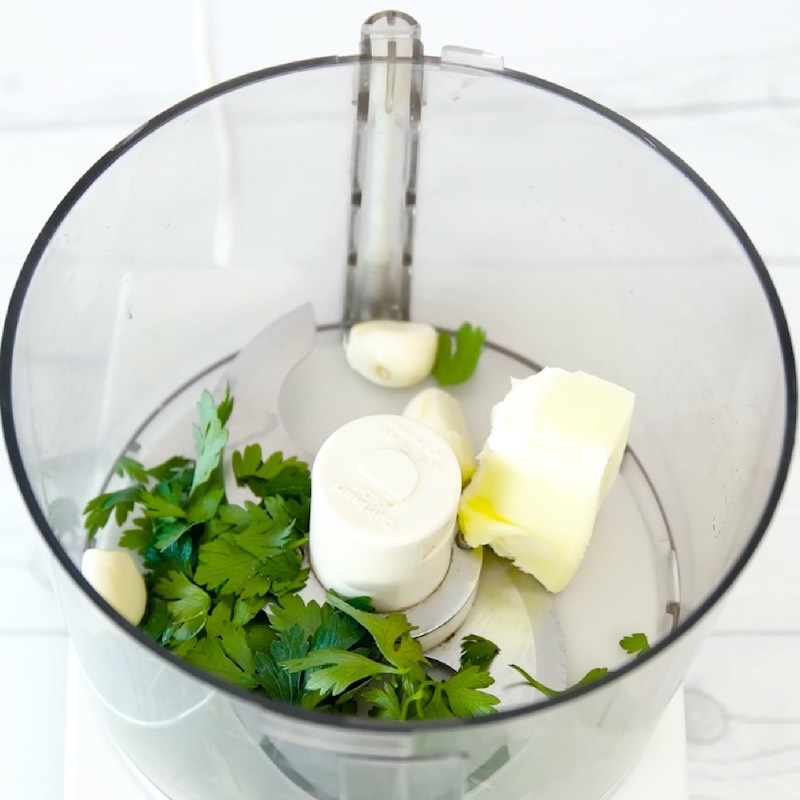 This photo shows butter, garlic and parsley in a food processor to make the garlic butter sauce for Garlic Butter Shrimp