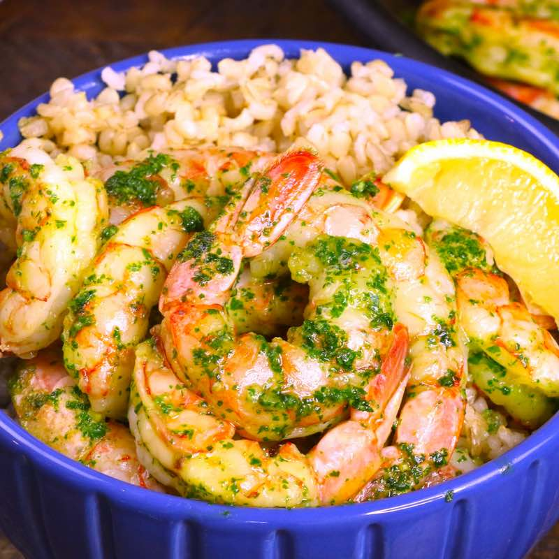 This photo shows garlic butter shrimp served on a bed of rice in a bowl