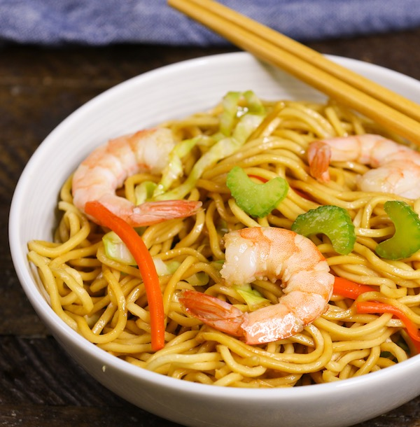 Shrimp Lo Mein with celery, red bell peppers and green onions in a serving bowl with chopsticks
